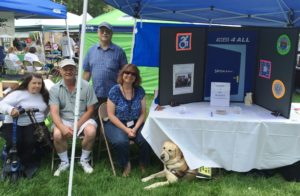 Image is of four people next to an A4A Spokane table display under a canopy.