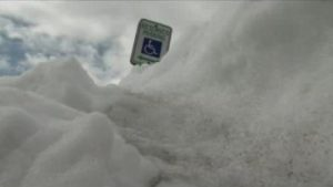 "image shows a standard ""reserved parking"" sign with the international wheelchair symbol surrounded by snow that is piled high enough to partially block the sign"