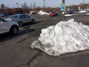 pile of snow partially covering a sidewalk, accessible parking space, and part of the sign